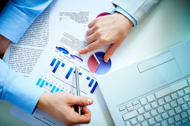 top-view-of-businessmen-analyzing-bar-charts-and-a-laptop_1098-344
