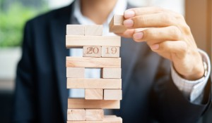 businessman-hand-placing-or-pulling-wooden-block-on-the-tower_42256-528