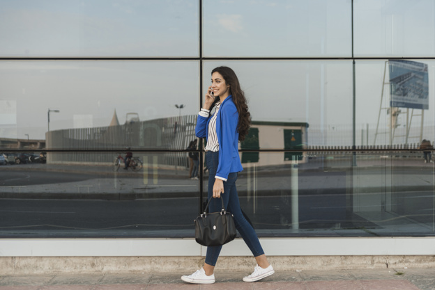 happy-young-woman-talking-on-the-phone-and-walking_23-2147605097