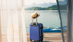 time-to-relax-suitcase-standing-on-the-floor-with-cap-out-the-room-travel-lifestyle_55877-4