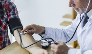 bearded-doctor-measuring-blood-pressure_23-2147896713