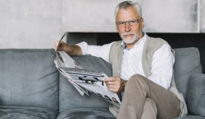 elderly-man-sitting-sofa-reading-newspaper_23-2147901076