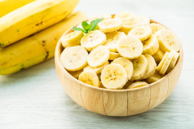 fatias-de-banana-amarela-crua-na-tigela-de-madeira_74190-2177