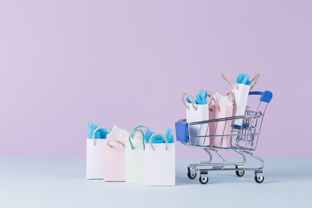 filled-miniature-cart-with-paper-shopping-bags-front-pink-background_23-2147892202