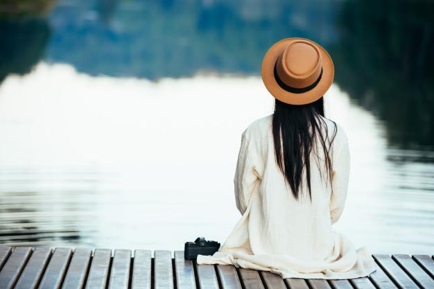 mulher-solitaria-sentado-na-jangada-a-beira-mar_1150-7466