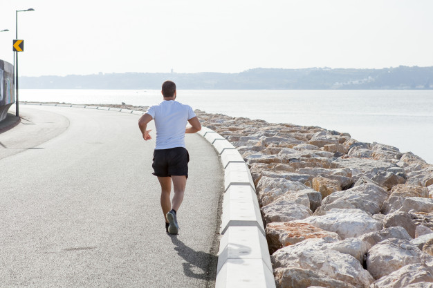 vista-traseira-do-homem-forte-que-corre-na-estrada-do-beira-mar_1262-5972