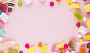 various-sweet-candies-forming-frame-pink-background_23-2147921695